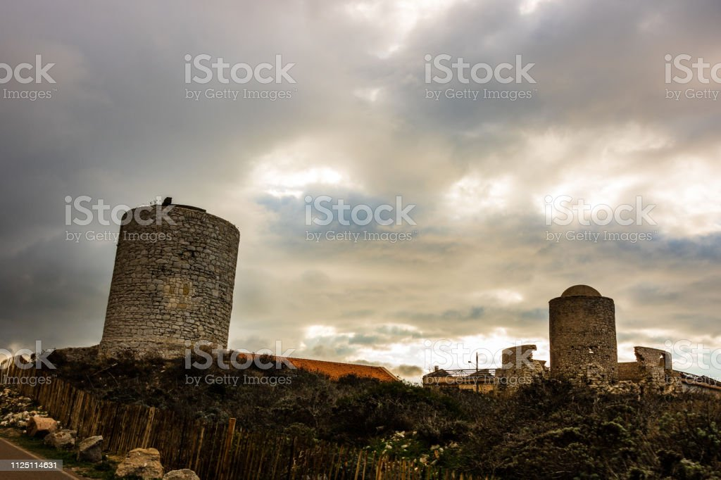 Ruins of an ancient stone mill built on the cliff top at Bonifacio in...