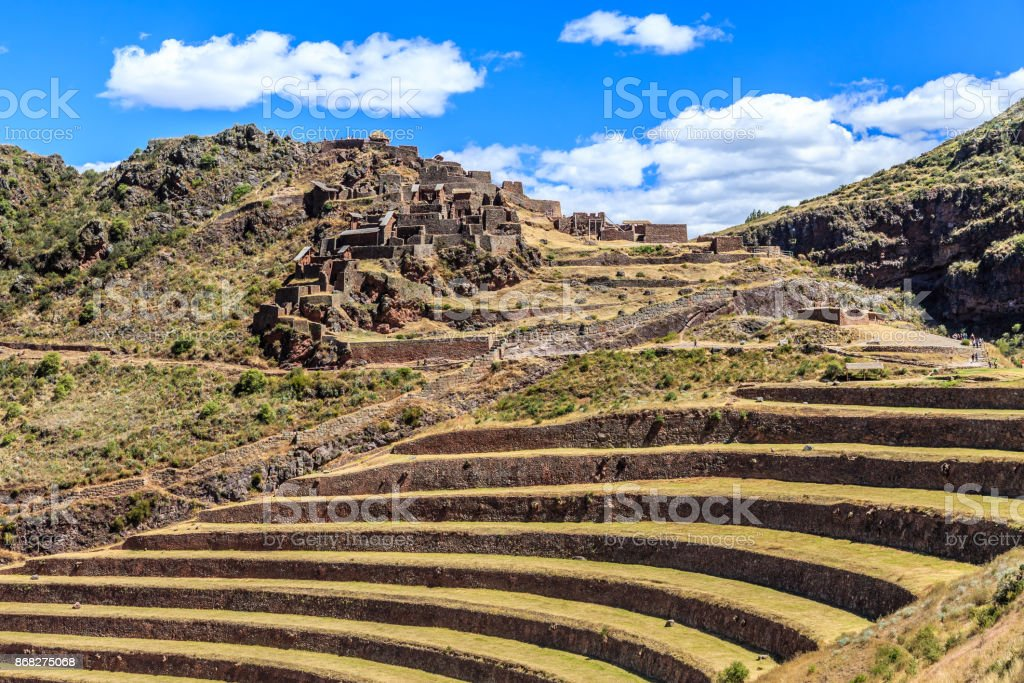 Ruins of ancient Incan city with terraces on the mountain with cloud sky in the background, Pisac, Peru stock photo