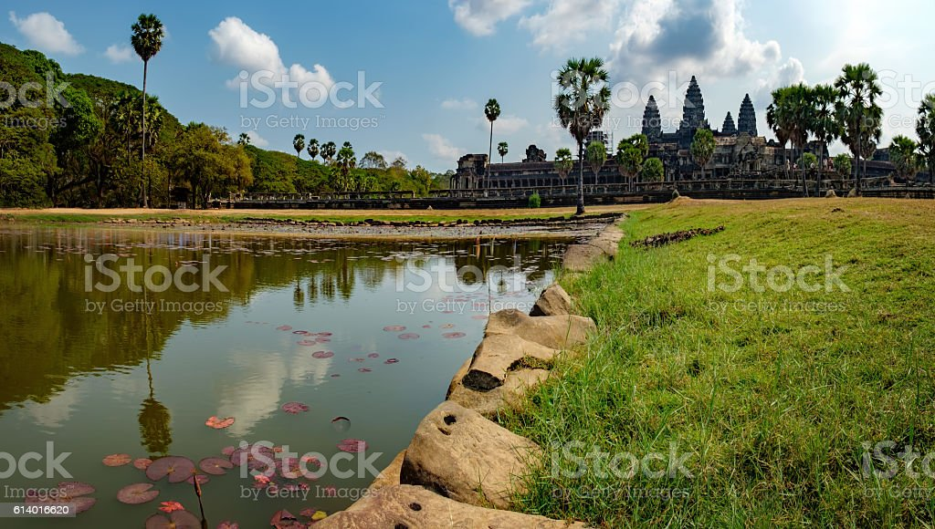 Ruins of Angkor Wat seen across pond with lilies, Cambodia. stock photo
