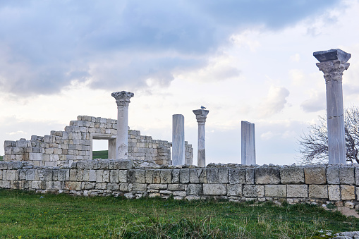 ruins of an ancient Greek basilica with columns against a winter cloudy sky