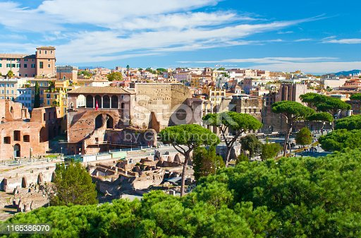 istock Ruins of Foro Traiano and Casa dei Cavalieri di Rodi among many high green trees. Old town of Rome, Italy. Sunny autumn day. Shot from above 1165386070