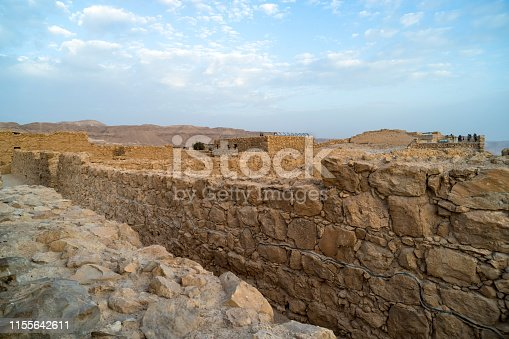 Ruins of fortress Masada, Israel. Close up of stone walls built many years ago on plateua on the cliff in Southern Israel. Remains of roman civilization in Israel against blue sky on a fine day.
