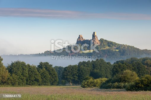 istock Ruins of old castle Trosky in Bohemian Paradise, Czech Republic. Ruins consist of two devasted towers on the woody hill. Morning landscape with misty atmosphere 1265644170