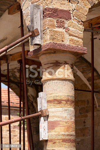 Detail (close-up) of ruins of old Greek Orthodox church made of sandstone in need of support (propped up) not to fall apart. Shallow depth of field. Blurred background. The image was captured with a prime lens and a full frame DSLR camera at low ISO resulting in large clean files.