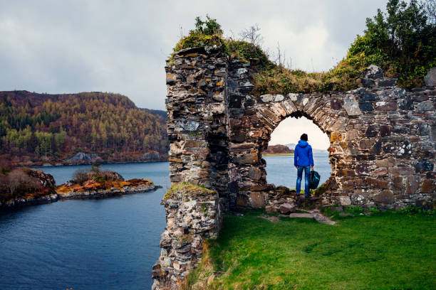 Ruins of Strome Castle, Loch Carron, Scotland Female tourist at the ruins of Strome Castle on the shores of Loch Carron in the Wester Ross region of Scotland. scottish highlands stock pictures, royalty-free photos & images