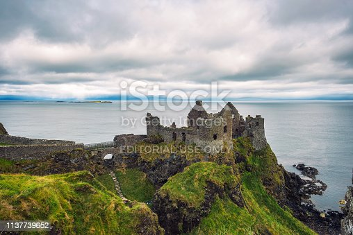 Ruins of the medieval Dunluce Castle with surrounding cliffs and Atlantic Ocean in the background, Northern Ireland