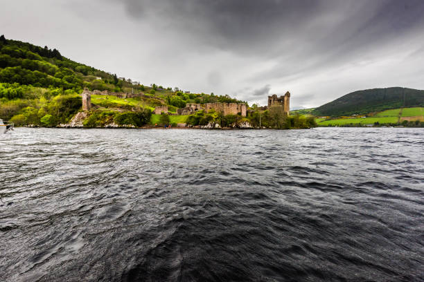 Ruins of Urquhart castle as seen from Loch Ness Ruins of the beautiful Urquhart castle and the hills containing the castle taken during boat ride on the loch ness. The gloomy day and the clouds provide a dramatic effect to the ruins. inverness scotland stock pictures, royalty-free photos & images
