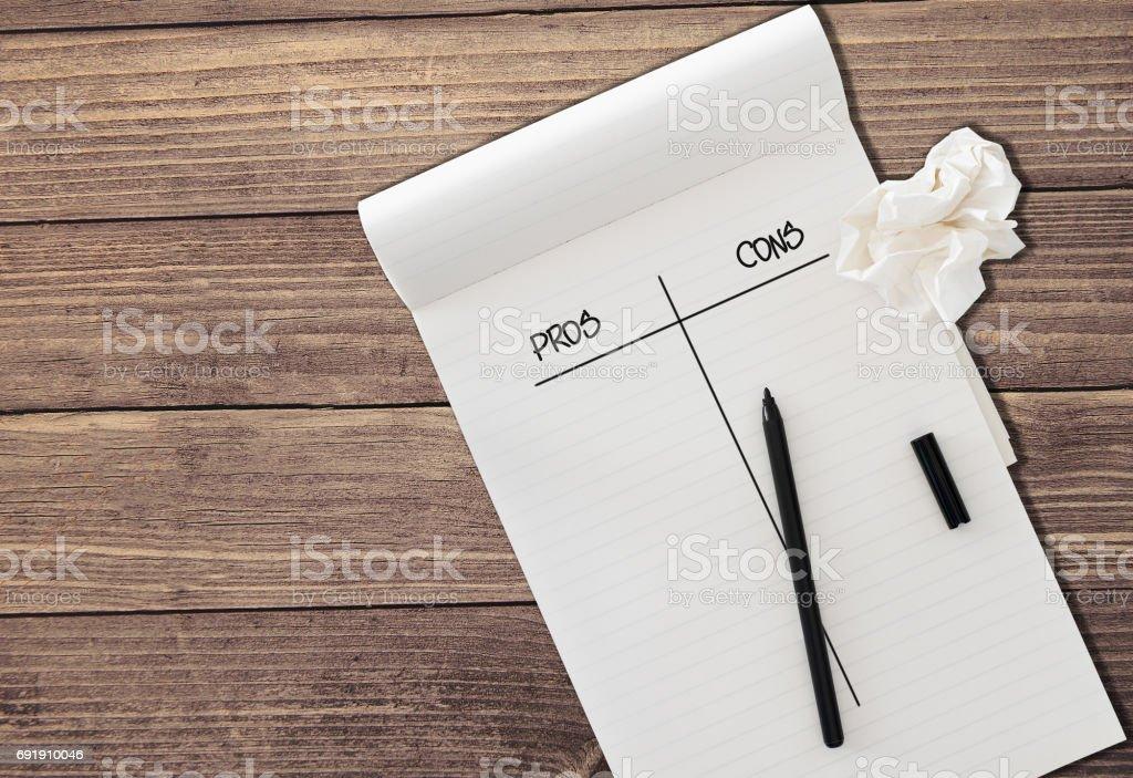 linierten Notizblock mit Wörtern pro und Kontra mit schwarzen Filz Filzstift und ein Stück zerknülltes Papier auf rustikalen Holztisch Hintergrund isoliert – Foto
