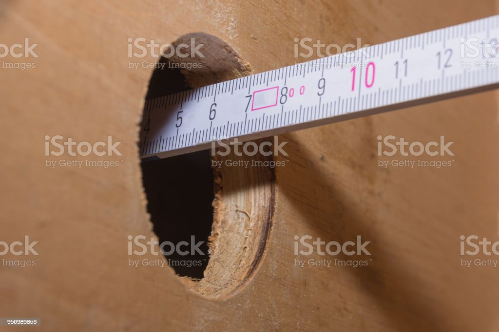 Ruler Meter Stick In Hole Of A Wooden Plate Stock Photo