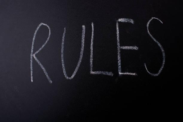 Rules written with chalk on blackboard stock photo
