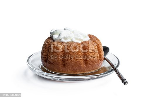 istock Rum baba decorated with whipped cream isolated on white 1287610548