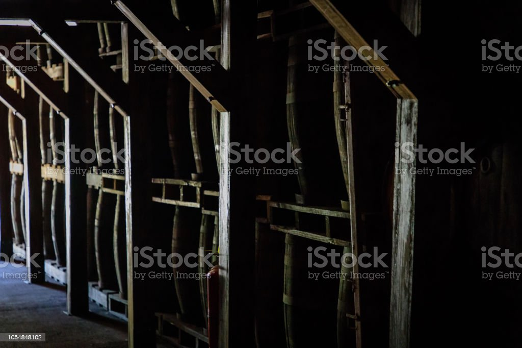 Rum or whiskey wooden barrels stacked in a warehouse stock photo