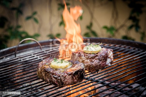 Rump steaks on the open fire. Being cooked with melted butter on the top of the meat. There is a big flame in the back ground. Busy being cooked on an open fire.
