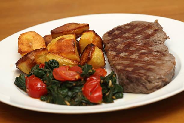 rumpsteak mit bratkartoffeln und blattspinat - rezept für rinderbraten stock-fotos und bilder