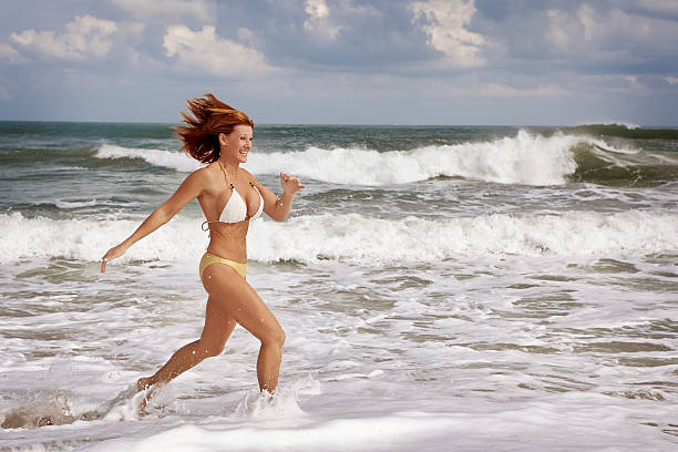 run at the beach - older women bikini stock pictures, royalty-free photos & images