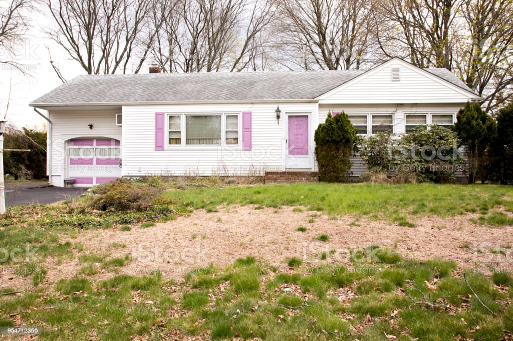 Run down house with dead lawn in foreground stock photo