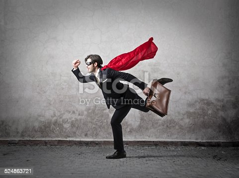 A businessman in an elegant suit and carrying a briefcase is wearing a red mantle and a black mask in order to hide his identity; he's running or flying as well