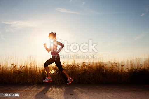 A mid-adult female runner runs during a cool fall sunset.