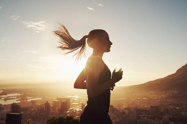 lauf mit der sonne - joggerin stock-fotos und bilder