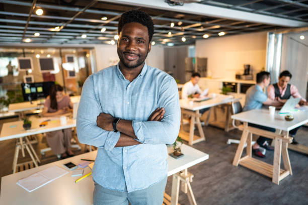 Run your company with confidence Portrait of Haitian man with crossed arms in the office in front of his desk haitian ethnicity stock pictures, royalty-free photos & images