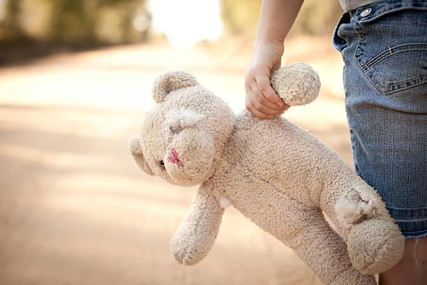 Runaway or Lost Girl Holding Old, Ragged Teddy Bear stock photo