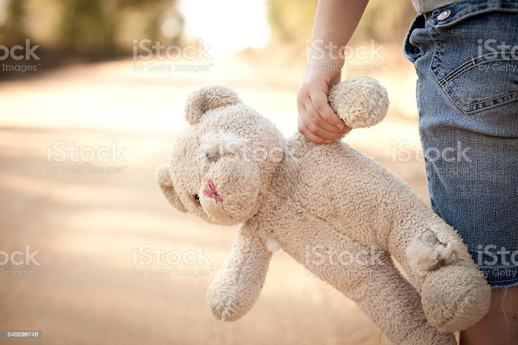 Runaway or Lost Girl Holding Old, Ragged Teddy Bear stock photo