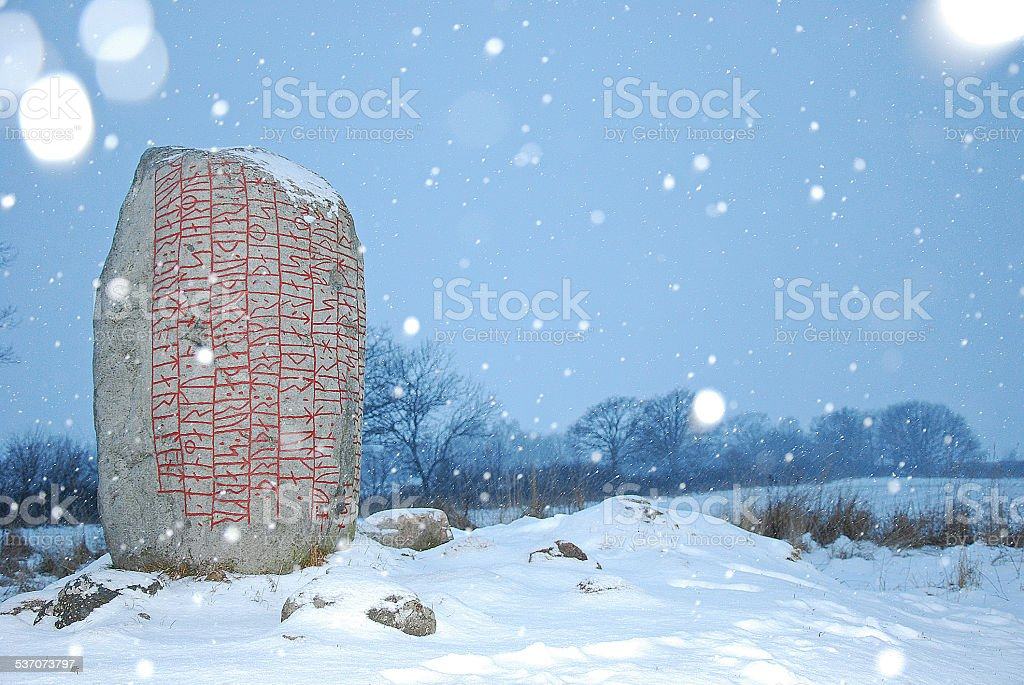 Rune stone in snowfall stock photo