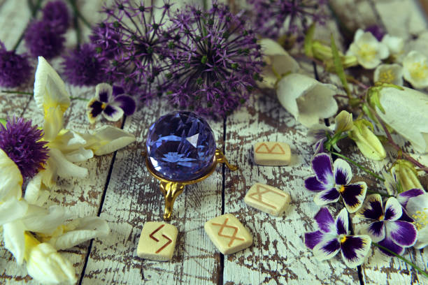 Runes and crystals with flowers on witch altar. stock photo