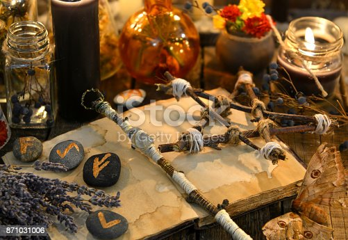 811119304 istock photo Runes, magic wand and pentagram on witch table 871031006