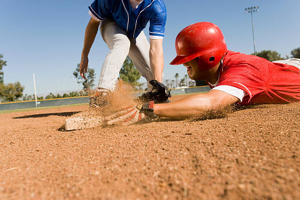 runner and infielder both reaching base - sliding stock photos and pictures