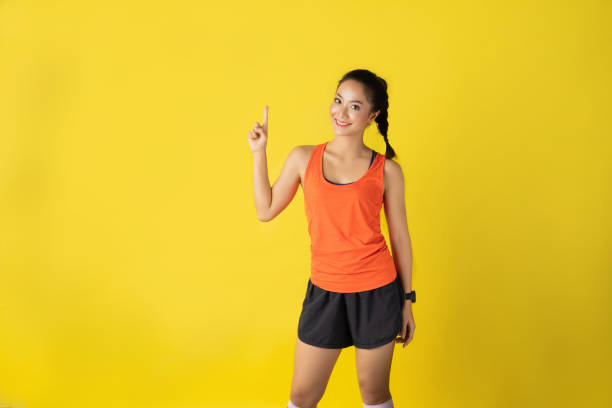 Runner asian woman announcer news on yellow background about race stock photo