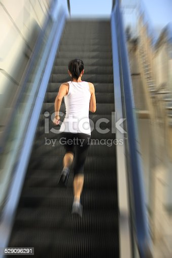 494003079istockphoto Runner athlete running on escalator stairs. 529096291