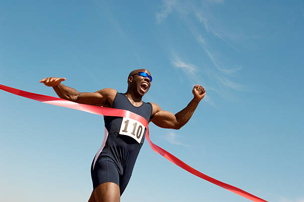 runner breaking finish line tape - finishing stock photos and pictures