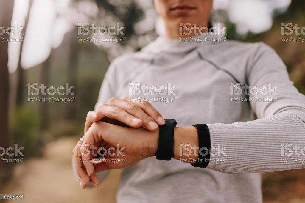 Runner checking fitness progress on her smart watch stock photo