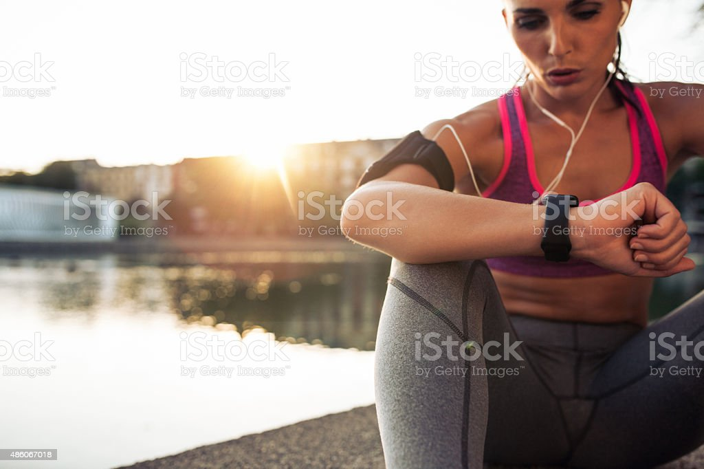 Runner checking her performance on fitness smart watch device stock photo