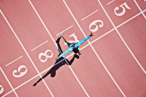 istock Runner crossing finishing line on track 102283878