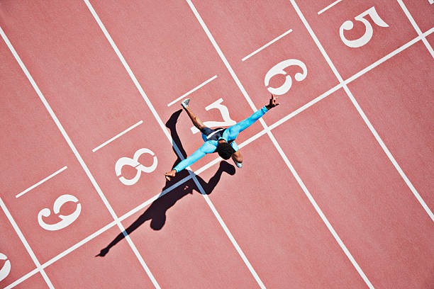 runner crossing finishing line on track - sport stock pictures, royalty-free photos & images
