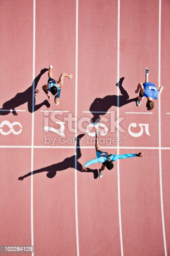 istock Runner crossing finishing line on track 102284129
