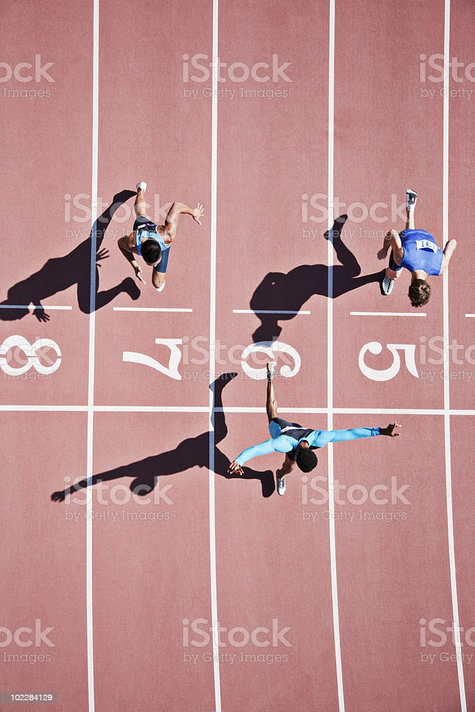 Runner crossing finishing line on track stock photo