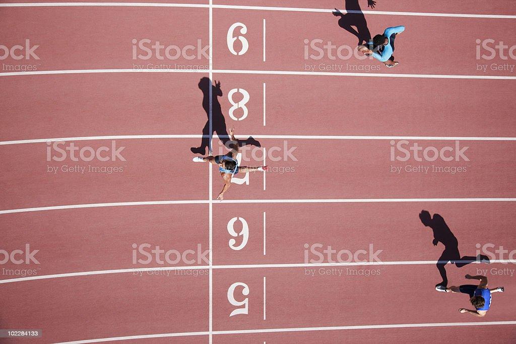 Runner crossing finishing line on track stock photo