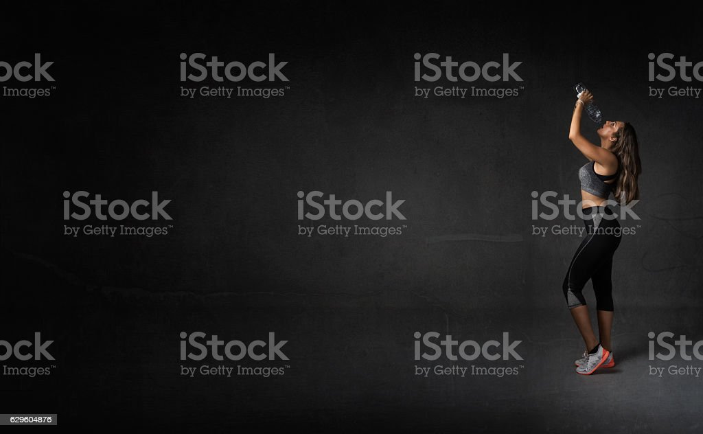 runner drinking with bottle on hand stock photo