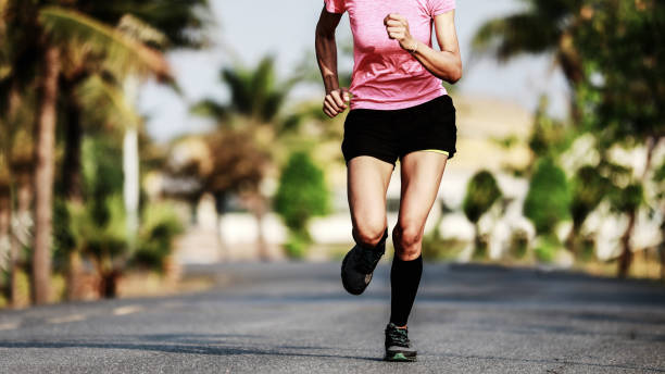 Pies de corredor corriendo sobre asfalto carretera - foto de stock