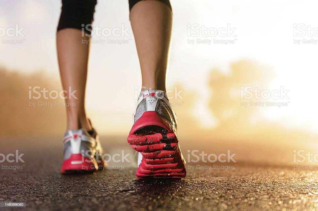 Runner feet running on road closeup on shoe. woman fitness sunrise...