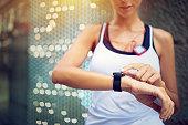 Runner girl is checking her smart watch