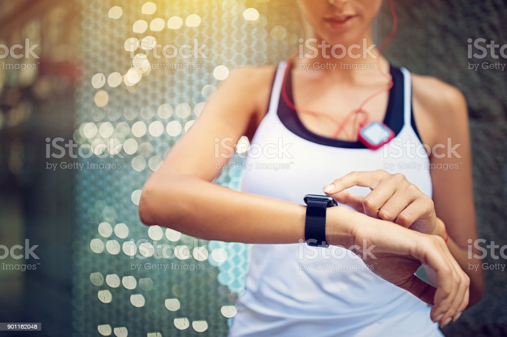 Runner girl is checking her smart watch stock photo
