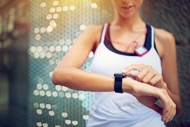 läufer-mädchen prüft ihre smartwatch - joggerin stock-fotos und bilder