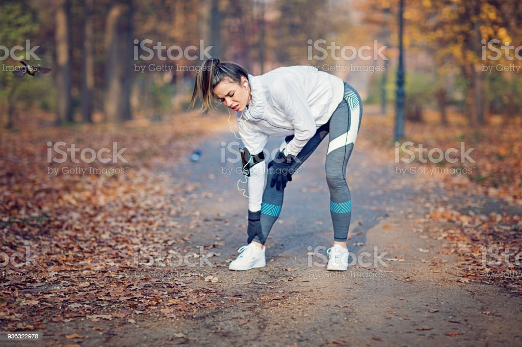 Runner girl is holding her injured leg stock photo