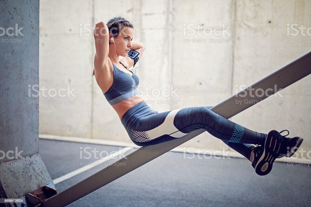 Runner girl is making sit ups stock photo