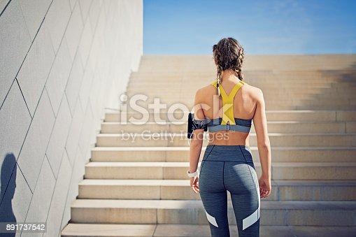 istock Runner girl is preparing to climb city stairs 891737542