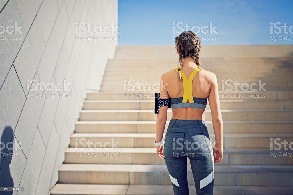 Runner girl is preparing to climb city stairs stock photo